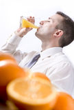 Oranges on table and man drinking orange juice. In the back Royalty Free Stock Photo