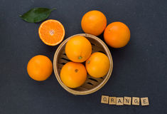 Oranges. On a table, three of them in a wooden container. Orange written in scrabble letter Stock Photos