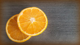 Oranges on the table. Two bright slices of juicy orange on a wooden background surface Stock Photography