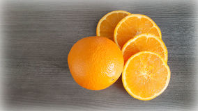 Oranges on the table. Whole orange and 4 slices on the gray wood surface Stock Images