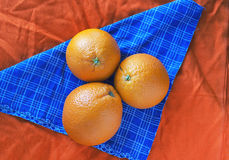Oranges. Two oranges on an orange cloth Royalty Free Stock Photos