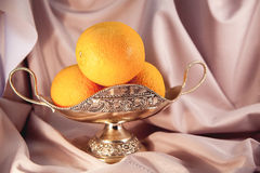 Oranges in a vase. Orange oranges in the vase lying on pink fabric Royalty Free Stock Photos