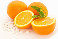 Oranges and Vitamins. Oranges and vitamin c pills on a white plate Royalty Free Stock Photos