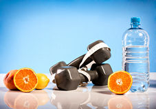 Oranges, weights and botte of water Stock Photo