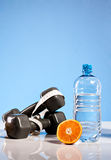 Oranges, weights and botte of water. Isolate on blue background Stock Images