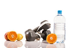 Oranges, weights and botte of water. Isolate on white background Stock Photography