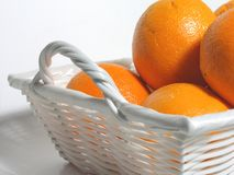Oranges in white basket. Oranges in white wicker basket royalty free stock photo