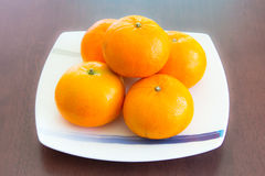 Oranges on the white dish. Some oranges on the white dish which is on wooden table Royalty Free Stock Image