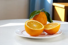Oranges on white plate Stock Images