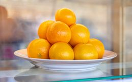Oranges on white plate. At market royalty free stock photos