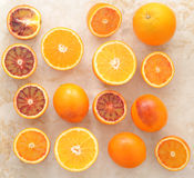 Oranges whole and cut in half on a marble background. background. From usual oranges and sicilian red bloody oranges. top view. blood orange Stock Image
