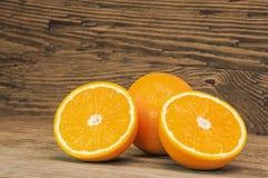 Oranges on a wooden background. Orange juicy oranges on a brown wooden background royalty free stock photos
