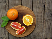 Oranges on a wooden background. Orange and red oranges with leaves on a wooden background royalty free stock image