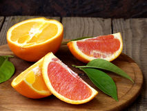 Oranges on a wooden background. Orange and red oranges with leaves on a wooden background royalty free stock photo