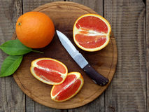 Oranges on a wooden background. Orange and red oranges with leaves on a wooden background stock photo