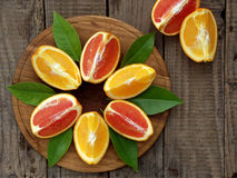 Oranges on a wooden background. Orange and red oranges with leaves on a wooden background stock image