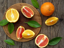 Oranges on a wooden background. Orange and red oranges with leaves on a wooden background royalty free stock photography