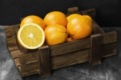 Oranges in a wooden box on a black background.  Royalty Free Stock Photo