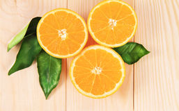 Oranges  on the wooden table. Oranges cut in half on the wooden table Royalty Free Stock Photo