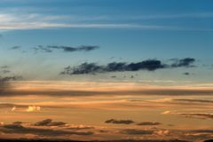 Long wispy clouds over the desert of southern Idaho sunset. Oranges yellows and blues in the skies with clouds as the sun begins to set Royalty Free Stock Photos