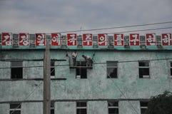 09/01/2018, orango, Corea del Nord: Due lavoratori stanno dipingendo una facciata di un blocco sovietico per l'anniversario 70 de fotografie stock libere da diritti