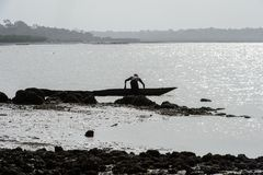 Unidentified local man stands near the boat on the coast of the. ORANGO ISLAND, GUINEA BISSAU - MAY 3, 2017: Unidentified local man stands near the boat on the stock photo