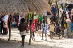 Unidentified local people gather together near the house in the. ORANGO ISLAND, GUINEA BISSAU - MAY 3, 2017: Unidentified local people gather together near the stock image