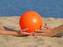 Oranje bal op het strandzand. Stock Afbeelding