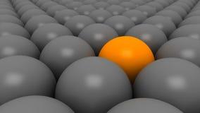 Oranje bal tussen grijze ballen Stock Fotografie