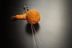 Oranje bal van garen met het breien en naalden stock fotografie