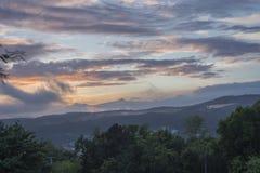 Oranje bewolkte hemel, zonsondergang over berg stock afbeelding