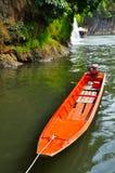 Oranje boot bij rivierkwai Stock Foto