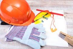 Oranje bouwvakker, Oordopje om lawaai te verminderen, veiligheidsbril, handschoenen, pen en het meten van band op houten achtergr royalty-vrije stock afbeelding