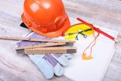Oranje bouwvakker, Oordopje om lawaai te verminderen, veiligheidsbril, handschoenen, pen en het meten van band op houten achtergr royalty-vrije stock afbeeldingen