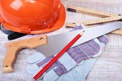Oranje bouwvakker, Oordopje om lawaai te verminderen, veiligheidsbril, handschoenen, pen en het meten van band op houten achtergr stock afbeelding
