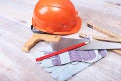 Oranje bouwvakker, oordopje, veiligheidsbril en handschoenen voor het werk Oordopje om lawaai op een witte achtergrond te vermind royalty-vrije stock foto