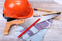 Oranje bouwvakker, oordopje, veiligheidsbril en handschoenen voor het werk Oordopje om lawaai op een witte achtergrond te vermind stock fotografie