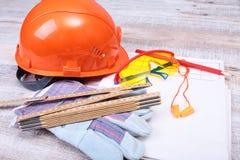Oranje bouwvakker, oordopje, veiligheidsbril en handschoenen voor het werk Oordopje om lawaai op een witte achtergrond te vermind royalty-vrije stock fotografie