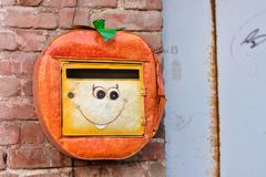 Oranje brievenbus met glimlach, brievenbus het hangen op de muur stock fotografie