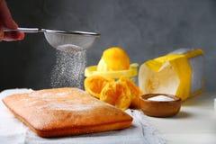 Oranje cake die gepoederde suiker en ingredi?nten op achtergrond verfraaien royalty-vrije stock fotografie
