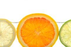 Oranje citroen en kalkplakken in water Stock Afbeeldingen