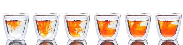 Oranje die kleur in glas water wordt uitgespreid Stock Afbeelding