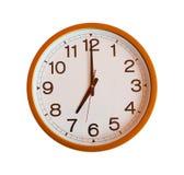 Oranje die muurklok in zeven uur wordt geïsoleerd Royalty-vrije Stock Fotografie