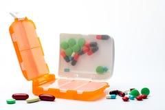 Oranje die pillenvakje met tabletten en capsulepillen op witte achtergrond met exemplaarruimte worden geïsoleerd royalty-vrije stock fotografie