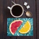 Oranje die plak en een kop van koffie op tribunes van gekleurde folie worden gemaakt Royalty-vrije Stock Foto