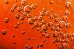 Oranje die water, lucht en olie voor een bruisend effect wordt gemengd Stock Afbeeldingen