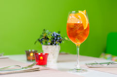 Oranje drank in glas op groene achtergrond stock afbeeldingen