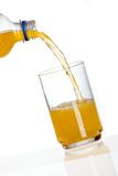 Oranje drank het gieten in glas Stock Fotografie