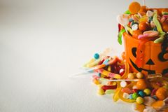 Oranje emmer met divers zoet voedsel tijdens Halloween op witte achtergrond stock foto's