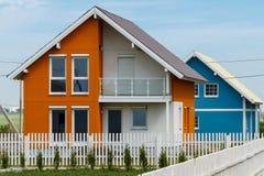Oranje en blauwe nieuwe huizen achter een witte omheining op een plattelandsgebied royalty-vrije stock afbeelding